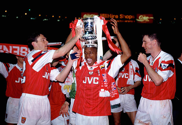 LONDON, UNITED KINGDOM - MAY 20: Arsenal goalscorers Ian Wright (c) and Andy Linighan (r) along with David O' Leary (l) celebrate with the trophy after the 1993 FA Cup Final replay between Arsenal and Sheffield Wednesday at Wembley Stadium on May 20, 1993 in London, England. (Photo by Simon Bruty/Allsport/Getty Images)