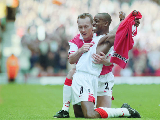 Ian Wright of Arsenal football club takes off his shirt and celebrates with team mate Lee Dixon after breaking Cliff Bastin's Arsenal goalscoring record of 178 goals with a hat-trick against Bolton Wanderers on13 September 1997 at the Arsenal Stadium, Highbury Stadium, London, United Kingdom. (Photo by Shaun Botterill/Getty Images).