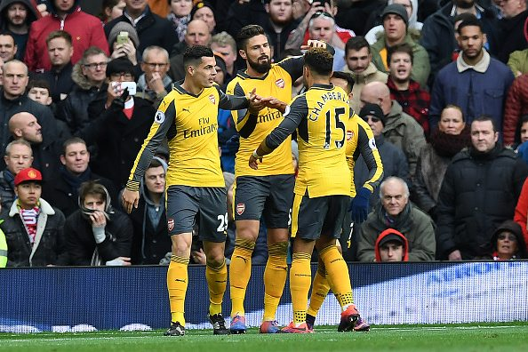 Arsenal's French striker Olivier Giroud (2L) celebrates scoring his team's first goal with Arsenal's English midfielder Alex Oxlade-Chamberlain (2R), Arsenal's Chilean striker Alexis Sanchez (R) and Arsenal's Swiss midfielder Granit Xhaka during the English Premier League football match between Manchester United and Arsenal at Old Trafford in Manchester, north west England, on November 19, 2016. / AFP / Paul ELLIS / RESTRICTED TO EDITORIAL USE. No use with unauthorized audio, video, data, fixture lists, club/league logos or 'live' services. Online in-match use limited to 75 images, no video emulation. No use in betting, games or single club/league/player publications. / (Photo credit should read PAUL ELLIS/AFP/Getty Images)