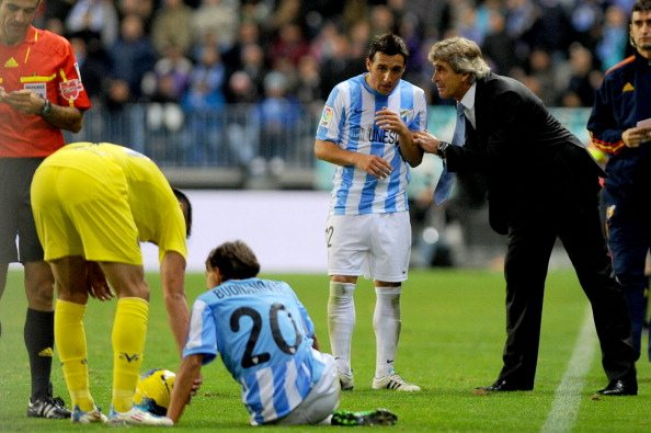 Malaga's Chilean coach Manuel Pellegrini (R) talks with midfielder Santiago Cazorla (2R) during the Spanish league football match Malaga CF vs Villarreal on November 28, 2011 at Rosaleda stadium in Malaga. AFP PHOTO/ JORGE GUERRERO (Photo credit should read Jorge Guerrero/AFP/Getty Images)