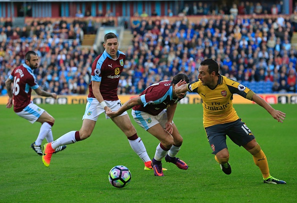 Arsenal's Spanish midfielder Santi Cazorla (R) vies with Burnley's Scottish midfielder George Boyd (2nd R), Burnley's Irish defender Stephen Ward (2nd L) and Burnley's Belgian midfielder Steven Defour (L) during the English Premier League football match between Burnley and Arsenal at Turf Moor in Burnley, north west England on October 2, 2016. / AFP / Lindsey PARNABY / RESTRICTED TO EDITORIAL USE. No use with unauthorized audio, video, data, fixture lists, club/league logos or 'live' services. Online in-match use limited to 75 images, no video emulation. No use in betting, games or single club/league/player publications. / (Photo credit should read LINDSEY PARNABY/AFP/Getty Images)