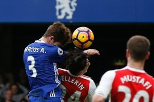 Chelsea's Spanish defender Marcos Alonso (L) rises above Arsenal's Spanish defender Hector Bellerin (C) to score the opening goal during the English Premier League football match between Chelsea and Arsenal at Stamford Bridge in London on February 4, 2017. / AFP / Ian KINGTON /
