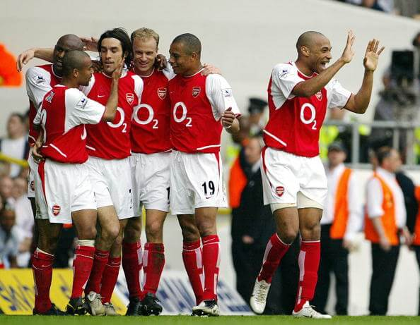 LONDON, UNITED KINGDOM: Arsenal's French forward Thierry Henry (R) celebrates as teammate Robert Pires (3rdL) is mobbed by Patrick Vieira (L), Ashley Cole (2ndL) Gilberto Silva (2ndR) and Dennis Bergkamp (3rdR) after scoring against Tottenham during their Premier League clash at White Hart Lane in north London, 25 April 2004. Arsenal leads 2-0 at half time. AFP PHOTO / ODD ANDERSEN