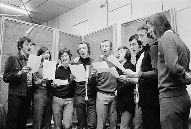 Arsenal footballers in a recording studio in London, UK, to record the single 'Good Old Arsenal', April 1971. They sang the song at the 1971 FA Cup Final in May. From left to right, Sammy Nelson, Peter Marinello, Pat Rice, Geoff Barnett, Bob Wilson, George Armstrong, Ray Kennedy, John Radford and Charlie George. (Photo by Les Lee/Daily Express/Getty Images)