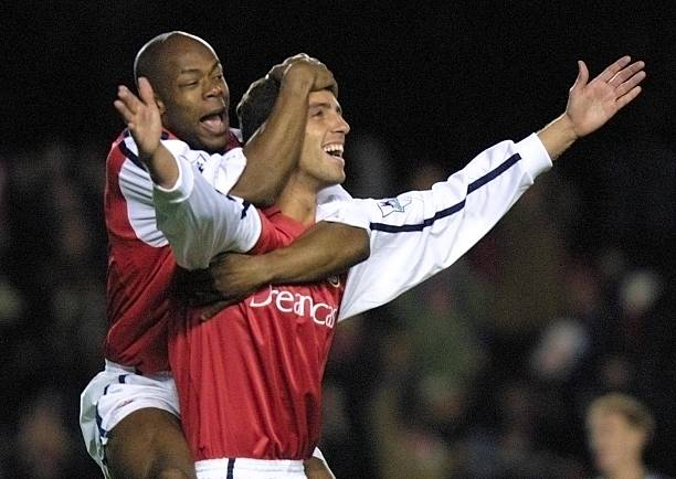 LONDON, UNITED KINGDOM: Arsenal's Sylvain Wiltord (L) jumps on teammate Edu (R) after he scored the opening goal against Grimsby Town's in The Worthington Cup 4th round match at Highbury in London 27 November 2001. AFP PHOTO Adrian DENNIS