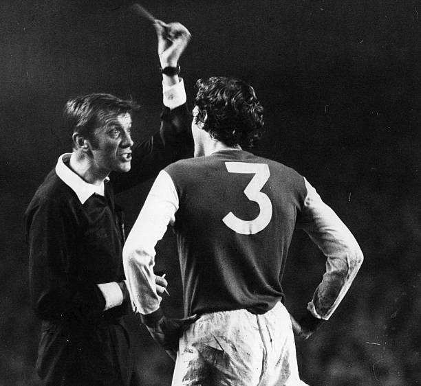 1976: During a match between London football clubs Arsenal and Chelsea, Arsenal player Sammy Nelson is booked by referee Ray Toseland, who holds up the yellow card. (Photo by Evening Standard/Getty Images)