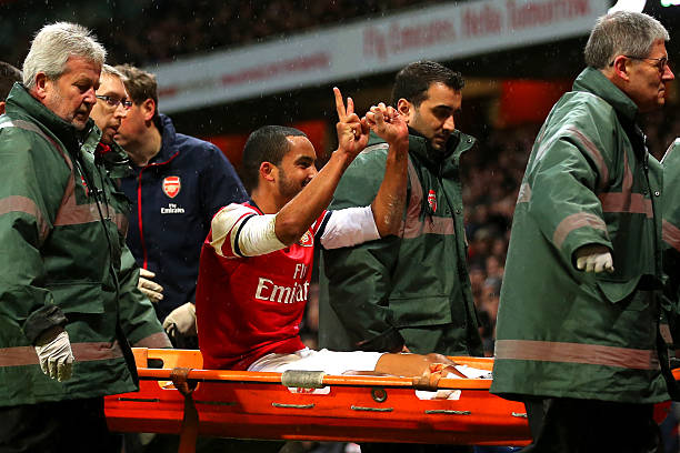 LONDON, ENGLAND - JANUARY 04: The injured Theo Walcott of Arsenal makes a 2-0 gesture to the Tottenham fans as he is stretchered off the pitch during the Budweiser FA Cup third round match between Arsenal and Tottenham Hotspur at Emirates Stadium on January 4, 2014 in London, England. (Photo by Clive Rose/Getty Images)