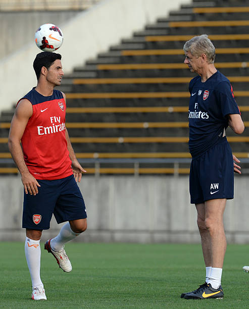 Arsenal midfielder Mikel Arteta (L) chats with head coach Arsene Wenger (R) during their training session in Nagoya on July 21, 2013. (TOSHIFUMI KITAMURA/AFP/Getty Images)