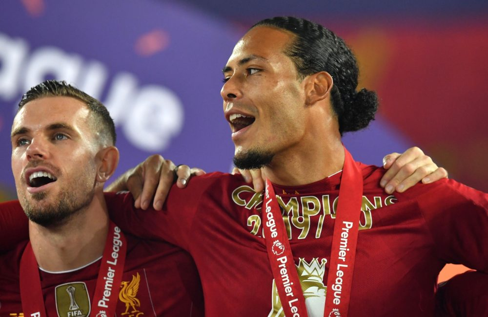 LIVERPOOL, ENGLAND - JULY 22: Jordan Henderson and Virgil van Dijk of Liverpool celebrate following the Premier League match between Liverpool FC and Chelsea FC at Anfield on July 22, 2020 in Liverpool, England. Football Stadiums around Europe remain empty due to the Coronavirus Pandemic as Government social distancing laws prohibit fans inside venues resulting in all fixtures being played behind closed doors. (Photo by Paul Ellis/Pool via Getty Images)