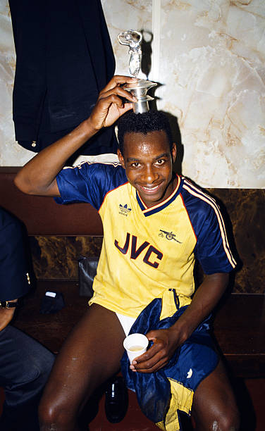 LIVERPOOL, UNITED KINGDOM - MAY 26: Arsenal goalscorer Michael Thomas celebrates in the dressing room with the Championship trophy lid after his goal sealed a 2-0 victory over rivals Liverpool to win the 1988/89 Football League title at Anfield on May 26, 1989 in Liverpool, England. (Photo by Allsport/Getty Images)