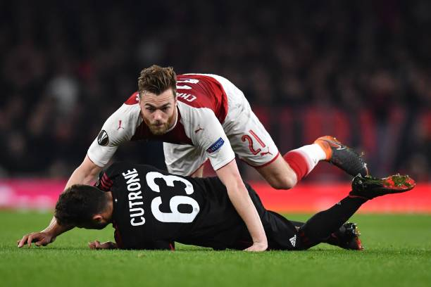 Arsenal's English defender Calum Chambers (R) and AC Milan's Italian striker Patrick Cutrone collide during the UEFA Europa League round of 16 second-leg football match between Arsenal and AC Milan at the Emirates Stadium in London on March 15, 2018. / AFP PHOTO / Ben STANSALL