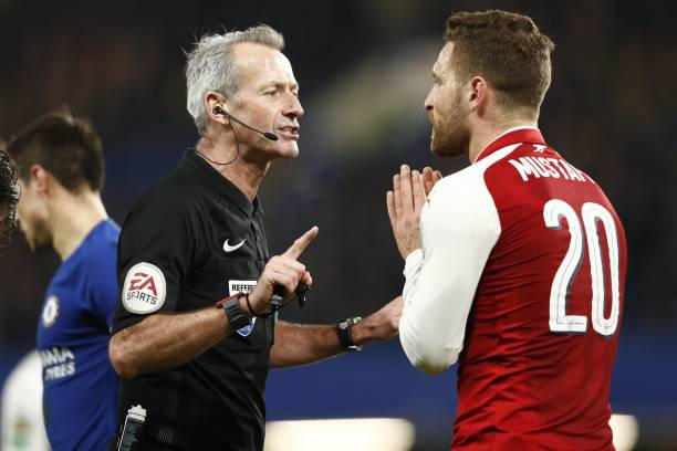 English referee Martin Atkinson (L) speaks with Arsenal's German defender Shkodran Mustafi during the English League Cup semi-final first leg football match between Chelsea and Arsenal at Stamford Bridge in London on January 10, 2018. / AFP PHOTO / Adrian DENNIS /