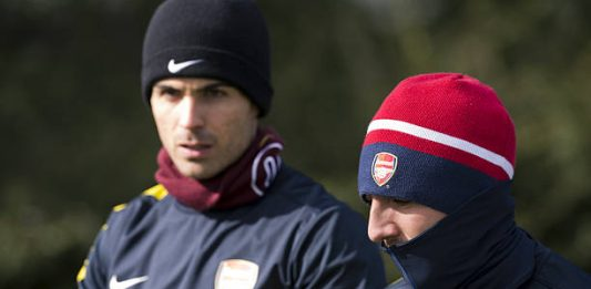 Arsenal's Spanish midfielder Mikel Arteta (L) and Arsenal's Spanish midfielder Santi Cazorla (R) walk to the pitch for a training session at the club's complex in London Colney on March 12, 2013 ahead of the team's last 16 UEFA Champions League football match against Bayern Munich in Germany on March 13. AFP PHOTO / ADRIAN DENNIS