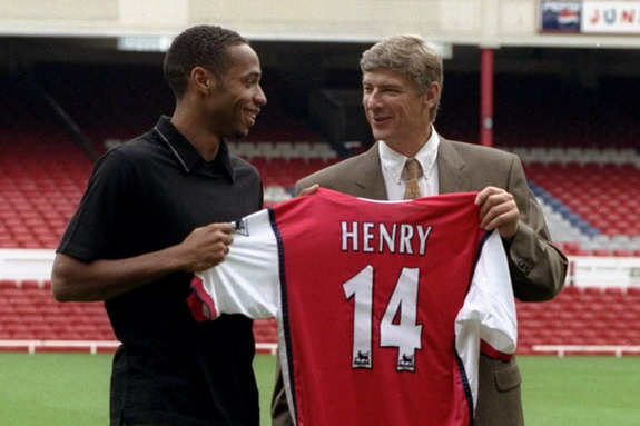 LONDON, UNITED KINGDOM - AUGUST 3: Striker Thierry Henry (L) holds up his shirt with Manager Arsene Wenger having been signed for Arsenal 03 August, 1999 from Juventus for an undisclosed fee. The 21-year old French international, who played under Arsene Wenger at AS Monaco was the leading scorer for the French World Cup winning squad at France '98 scoring three goals during the tournament. (Photo credit SINEAD LYNCH/AFP/Getty Images)