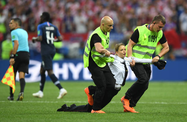 MOSCOW, RUSSIA - JULY 15: A pitch invader is being taken during the 2018 FIFA World Cup Final between France and Croatia at Luzhniki Stadium on July 15, 2018 in Moscow, Russia. (Photo by Shaun Botterill / Getty Images)