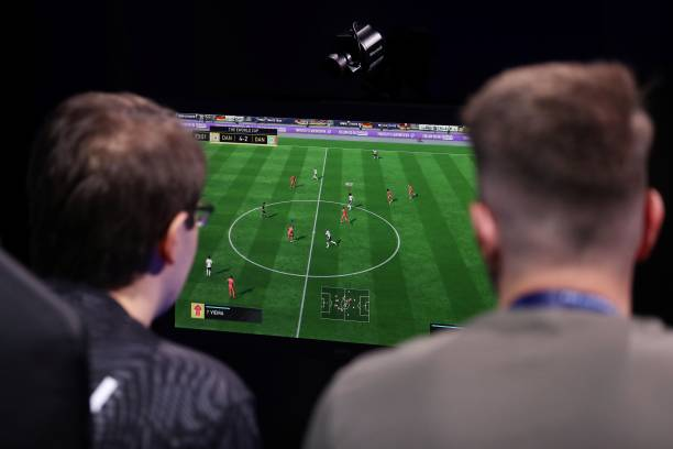 A player (L) competes on in the group stages of the FIFA eWorld Cup Grand Final, at the O2 in London on August 2, 2018. - The FIFA eWorld Cup Grand Final 2018 will see 32 finalists battle it out for the main prize the title of FIFA eWorld Cup champion, and pocket USD 250,000 in prize money. (Photo by Daniel LEAL-OLIVAS / AFP)