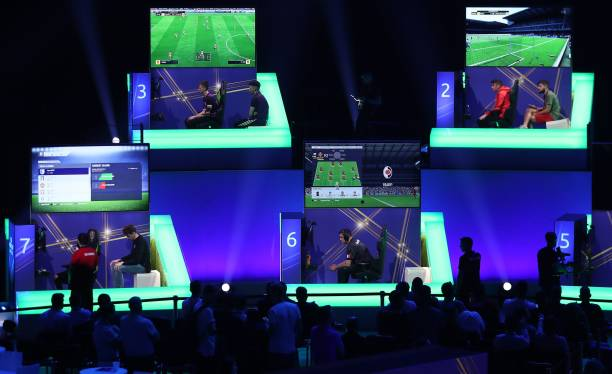 Players compete on Microsoft Xbox and Sony Playstation games consoles in the group stages of the FIFA eWorld Cup Grand Final, at the O2 in London on August 2, 2018. - The FIFA eWorld Cup Grand Final 2018 will see 32 finalists battle it out for the main prize the title of FIFA eWorld Cup champion, and pocket USD 250,000 in prize money. (Photo by Daniel LEAL-OLIVAS / AFP)