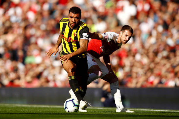 LONDON, ENGLAND - SEPTEMBER 29: Troy Deeney of Watford takes the ball away from Aaron Ramsey (R) of Arsenal during the Premier League match between Arsenal FC and Watford FC at Emirates Stadium on September 29, 2018 in London, United Kingdom. (Photo by Julian Finney/Getty Images)