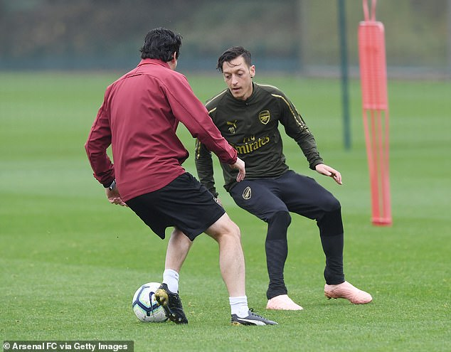 Unai Emery tries the shoulder drop on Mesut Özil / Arsenal FC via Getty Images