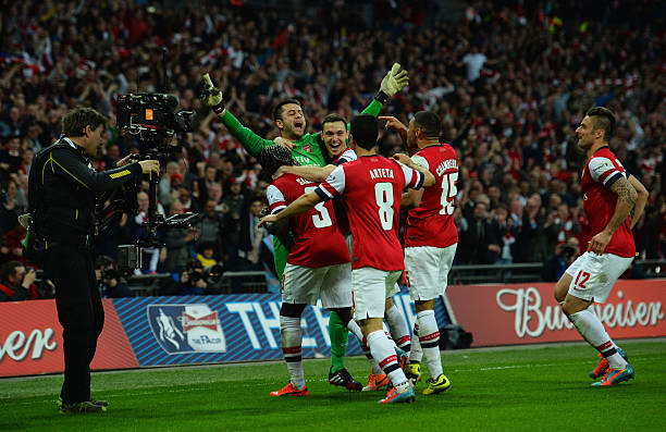 LONDON, ENGLAND - APRIL 12: Lukasz Fabianski of Arsenal celebrates winning the penalty shoot out with team mates during the FA Cup Semi-Final match between Wigan Athletic and Arsenal at Wembley Stadium on April 12, 2014 in London, England.  (Photo by Shaun Botterill/Getty Images)