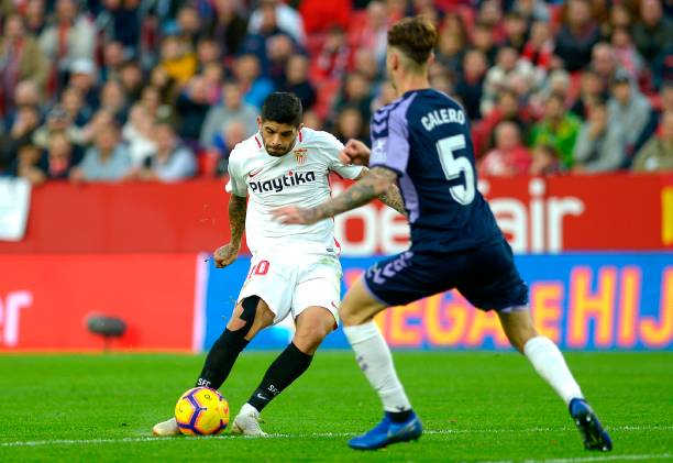Sevilla's Argentinian midfielder Ever Banega (L) vies for the ball with Real Valladolid's Spanish defender Fernando Calero (R) during the Spanish league football match Sevilla FC against Real Valladolid FC at the Ramon Sanchez Pizjuan stadium in Sevilla on November 25, 2018. (Photo by CRISTINA QUICLER / AFP)