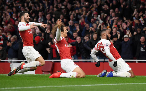 LONDON, ENGLAND - DECEMBER 02: Alexandre Lacazette of Arsenal celebrates with teammates after scoring his team's third goal during the Premier League match between Arsenal FC and Tottenham Hotspur at Emirates Stadium on December 1, 2018 in London, United Kingdom. (Photo by Shaun Botterill/Getty Images)