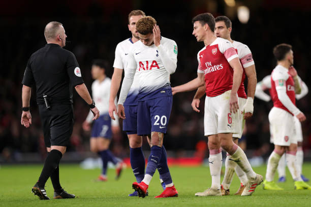 LONDON, ENGLAND - DECEMBER 19: Dele Alli of Tottenham Hotspur reacts after being hit by a water bottle during the Carabao Cup Quarter Final match between Arsenal and Tottenham Hotspur at Emirates Stadium on December 19, 2018 in London, United Kingdom. (Photo by Alex Morton/Getty Images)