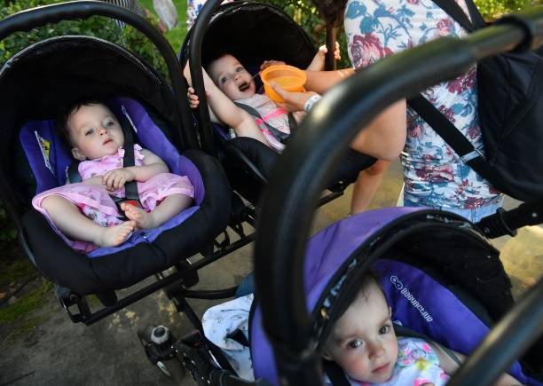 A mother feeds her triplets as they attend the children's Festival Of Twins, in Kiev, on August 11, 2018. - Representatives of the Ukrainian Records Book set the new country's record at more than 200 pairs of twins and triplets during the event. (Photo by Sergei SUPINSKY / AFP)
