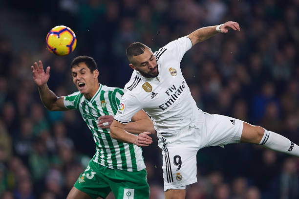 SEVILLE, SPAIN - JANUARY 13: Aissa Mandi of Real Betis Balompie (L) competes for the ball with Karim Benzema of Real Madrid CF (R) during the La Liga match between Real Betis Balompie and Real Madrid CF at Estadio Benito Villamarin on January 13, 2019 in Seville, Spain. (Photo by Aitor Alcalde/Getty Images)