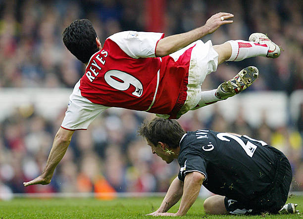 LONDON, UNITED KINGDOM: Arsenal's Jose Reyes (top) flies over Gary Neville of Manchester United during their FA Premier League clash at Highbury in London, 28 March 2004. AFP PHOTO / ODD