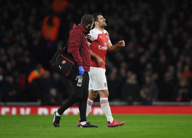 LONDON, ENGLAND - JANUARY 25: An injured Sokratis Papastathopoulos of Arsenal is given assistance during the FA Cup Fourth Round match between Arsenal and Manchester United at Emirates Stadium on January 25, 2019 in London, United Kingdom. (Photo by Mike Hewitt/Getty Images)