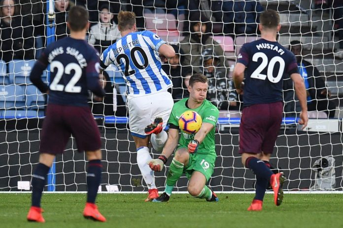 Arsenal's German goalkeeper Bernd Leno (2R) saves a shot from Huddersfield Town's Belgian striker Laurent Depoitre (2L) during the English Premier League football match between Huddersfield Town and Arsenal at the John Smith's stadium in Huddersfield, northern England on February 9, 2019. (Photo by Oli SCARFF / AFP)