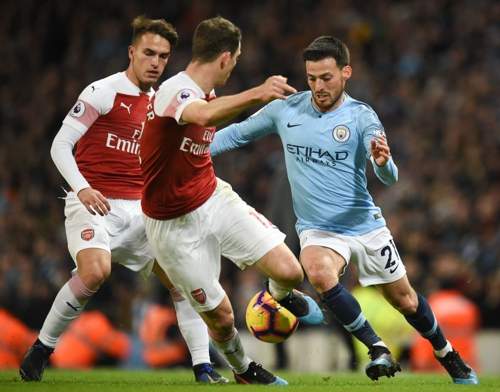 Manchester City's Spanish midfielder David Silva (R) takes on Arsenal's Swiss defender Stephan Lichtsteiner (C) during the English Premier League football match between Manchester City and Arsenal at the Etihad Stadium in Manchester, north west England, on February 3, 2019. (Photo by OLI SCARFF / AFP / Getty Images)