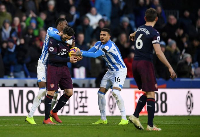 HUDDERSFIELD, ENGLAND - FEBRUARY 09: Adama Diakhaby and Karlan Grant of Huddersfield Town attempt to get the ball off Sead Kolasinac of Arsenal after their team's first goal during the Premier League match between Huddersfield Town and Arsenal FC at John Smith's Stadium on February 9, 2019 in Huddersfield, United Kingdom. (Photo by Gareth Copley/Getty Images)
