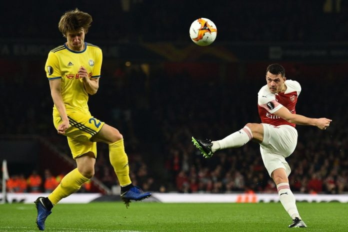 BATE Borisov's Belarusian midfielder Dmitri Baga (L) takes evasive action as Arsenal's Swiss midfielder Granit Xhaka shoots over during the UEFA Europa League round of 32, 2nd leg football match between Arsenal and Bate Borisov at the Emirates stadium in London on February 21, 2019. (Photo by Glyn KIRK / AFP / Getty Images)