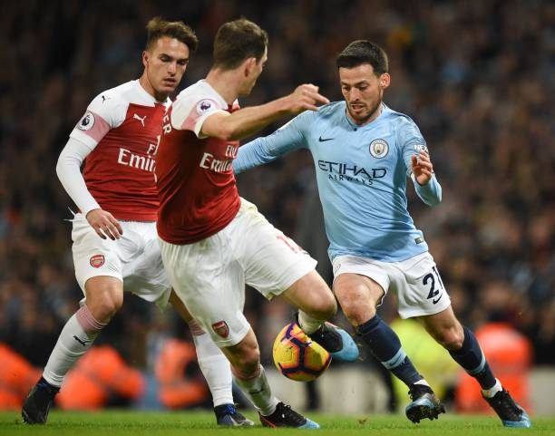 Manchester City's Spanish midfielder David Silva (R) takes on Arsenal's Swiss defender Stephan Lichtsteiner (C) during the English Premier League football match between Manchester City and Arsenal at the Etihad Stadium in Manchester, north west England, on February 3, 2019. (Photo by Oli SCARFF / AFP)
