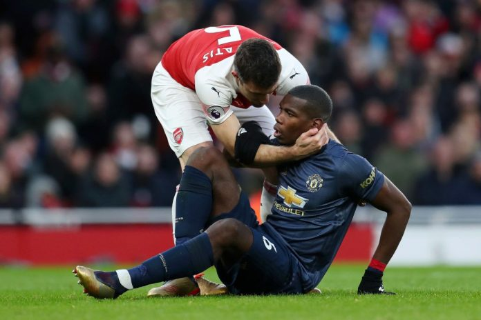 LONDON, ENGLAND - MARCH 10: Paul Pogba of Manchester United is helped up by Sokratis Papastathopoulos of Arsenal during the Premier League match between Arsenal FC and Manchester United at Emirates Stadium on March 10, 2019 in London, United Kingdom. (Photo by Catherine Ivill/Getty Images)