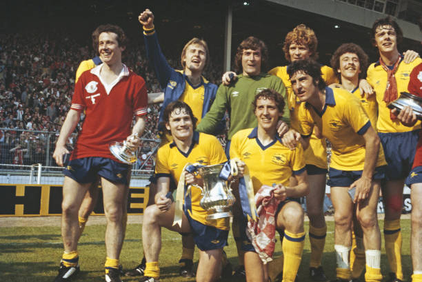 LONDON, UNITED KINGDOM - MAY 12: Arsenal player Liam Brady (l) wearing a Manchester United shirt leads the celebrations after their 3-2 victory in the 1979 FA Cup Final at Wembley Stadium on May 12, 1979 with back row, left to right David Price, Pat Jennings, Willie Young, Alan Sunderland and David O' Leary and front row Pat Rice and Sammy Nelson with cup and Brian Talbot (standing) (Photo by Allsport/Getty Images)