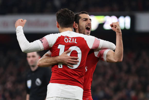 LONDON, ENGLAND - FEBRUARY 27: Henrikh Mkhitaryan of Arsenal celebrates scoring his sides second goal with Mesut Ozil of Arsenal during the Premier League match between Arsenal FC and AFC Bournemouth at Emirates Stadium on February 27, 2019 in London, United Kingdom. (Photo by Catherine Ivill/Getty Images)