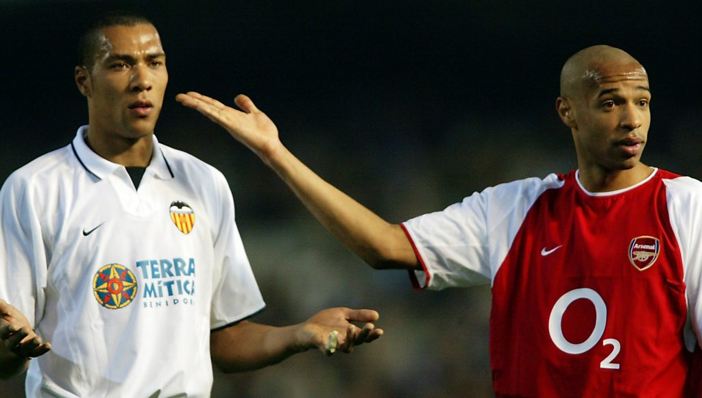 VALENCIA - MARCH 19: Thierry Henry (right) of Arsenal with John Carew (left) of Valencia show they are the same colour to try to calm the fans down after Thierry Henry gets racial abuse from the home fans during the UEFA Champions League Second Phase Group B match held on March 19, 2003 at Mestalla Camp Del Valencia, in Valencia, Spain. Valencia won the match 2-1. (Photo by Ben Radford/Getty Images)