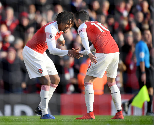 LONDON, ENGLAND - DECEMBER 22: Alex Iwobi of Arsenal celebrates after scoring his team's third goal with Mesut Ozil of Arsenal during the Premier League match between Arsenal FC and Burnley FC at Emirates Stadium on December 22, 2018 in London, United Kingdom. (Photo by Shaun Botterill/Getty Images)