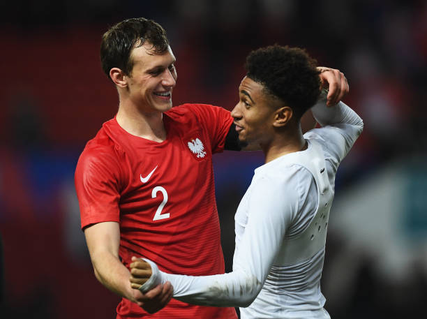 BRISTOL, ENGLAND - MARCH 21: Krystian Bielik of Poland and Reiss Nelson of England share a joke after the U21 International Friendly match between England and Poland at Ashton Gate on March 21, 2019 in Bristol, England. (Photo by Harry Trump/Getty Images)