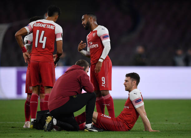 NAPLES, ITALY - APRIL 18: Aaron Ramsey of Arsenal recieves treatment for an injury during the UEFA Europa League Quarter Final Second Leg match between S.S.C. Napoli and Arsenal at Stadio San Paolo on April 18, 2019 in Naples, Italy. (Photo by Stuart Franklin/Getty Images)