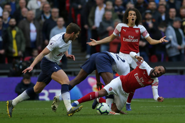 Arsenal's French striker Alexandre Lacazette (R) is fouled by Tottenham Hotspur's Kenyan midfielder Victor Wanyama (C) during the English Premier League football match between Tottenham Hotspur and Arsenal at Wembley Stadium in London, on March 2, 2019. (Photo by Daniel LEAL-OLIVAS / AFP)