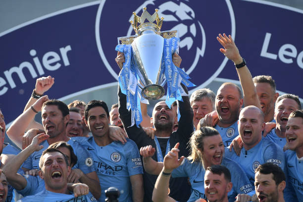 BRIGHTON, ENGLAND - MAY 12: Manchester City manager Pep Guardiola holds the winner's trophy aloft after the Premier League match between Brighton & Hove Albion and Manchester City at American Express Community Stadium on May 12, 2019 in Brighton, United Kingdom. (Photo by Mike Hewitt/Getty Images)