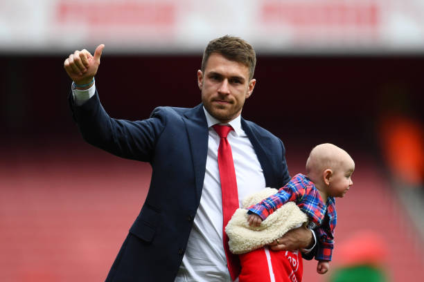 LONDON, ENGLAND - MAY 05: Aaron Ramsey of Arsenal, holding one of his children, acknowledges the crowd as he says farewell to the club following the Premier League match between Arsenal FC and Brighton & Hove Albion at Emirates Stadium on May 05, 2019 in London, United Kingdom. (Photo by Clive Mason/Getty Images)