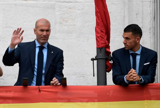 Real Madrid's French coach Zinedine Zidane (L) and Real Madrid's Spanish midfielder Daniel Ceballos greet supporters from the balcony of the headquarters of the regional government of Madrid at the Puerta del Sol square in Madrid on May 27, 2018 as they celebrate their third Champions League title in a row in Kiev. (Photo by OSCAR DEL POZO / AFP)