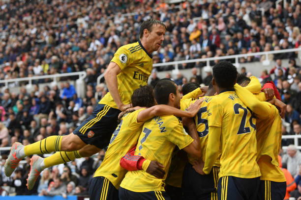 NEWCASTLE UPON TYNE, ENGLAND - AUGUST 11: Pierre-Emerick Aubameyang of Arsenal (obscured) celebrates with teammates as Nacho Monreal jumps on top after scoring his team's first goal during the Premier League match between Newcastle United and Arsenal FC at St. James Park on August 11, 2019 in Newcastle upon Tyne, United Kingdom. (Photo by Stu Forster/Getty Images)