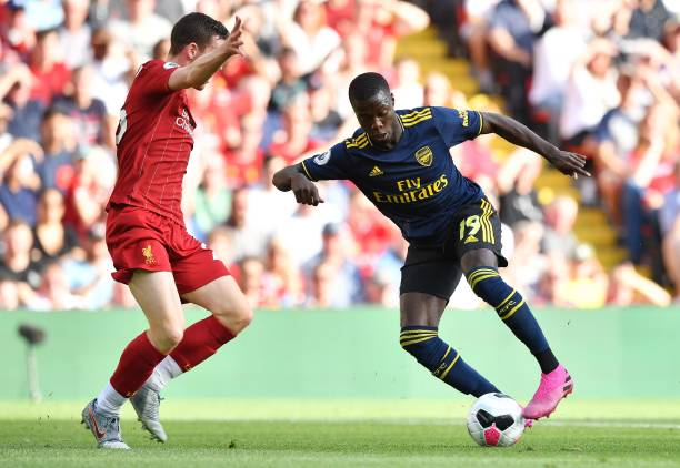 Arsenal's French-born Ivorian midfielder Nicolas Pepe (R) controls the ball in front of Liverpool's Scottish defender Andrew Robertson (L) during the English Premier League football match between Liverpool and Arsenal at Anfield in Liverpool, north west England on August 24, 2019. (Photo by Ben STANSALL / AFP)