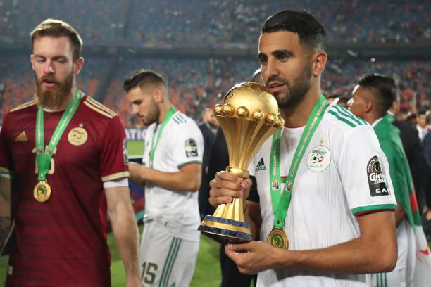Algeria's forward Riyad Mahrez (R) celebrates with the trophy during the 2019 Africa Cup of Nations (CAN) Final football match between Senegal and Algeria at the Cairo International Stadium in Cairo on July 19, 2019. (Photo by Khaled DESOUKI / AFP)